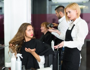 Displeased young girl has a serious conversation with the hairdresser
