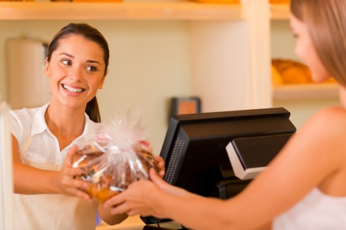 Please enjoy! Beautiful young female baker giving cookies to customer and smiling